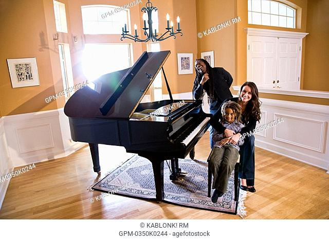Portrait of mixed race family sitting around piano