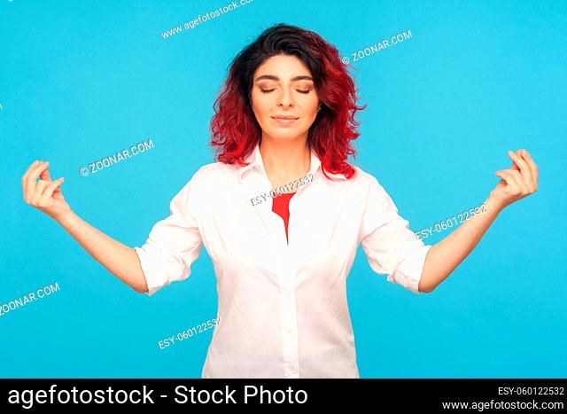Relaxation and harmony. Portrait of peaceful hipster woman with fancy red hair keeping hands in mudra gesture, practicing breath techniques, meditation