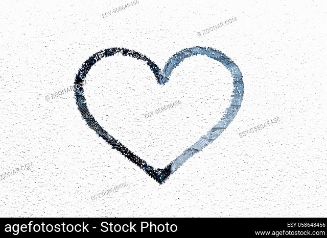 Heart drawn on a glass covered with fresh Christmas snow