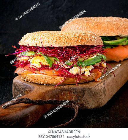 Two Bagels with salted salmon, spinach, beetroot sprouts, avocado and scrambled egg on wooden chopping board over old wood black background