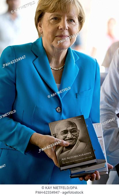 German Chancellor Angela Merkel holds up a book about independence hero Mahatma Gandhi at his memorial in New Dehli, India, 05 October 2015