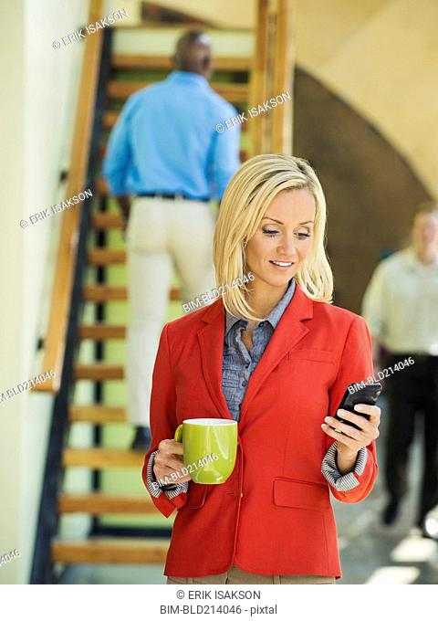 Businesswoman using cell phone near staircase