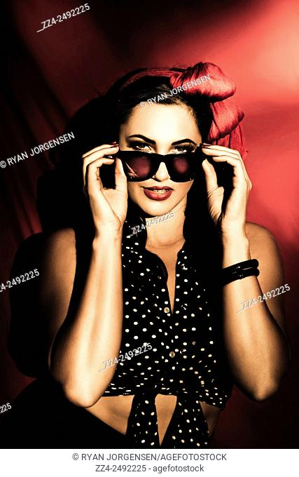Beautiful Hispanic brunette model in pin-up style fashion with hair bow and dark sunshades. Accessorize