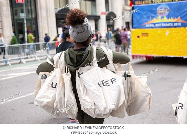 Uber, as sponsor, distributes goodie bags to spectators in New York at the first Nepal Day Parade