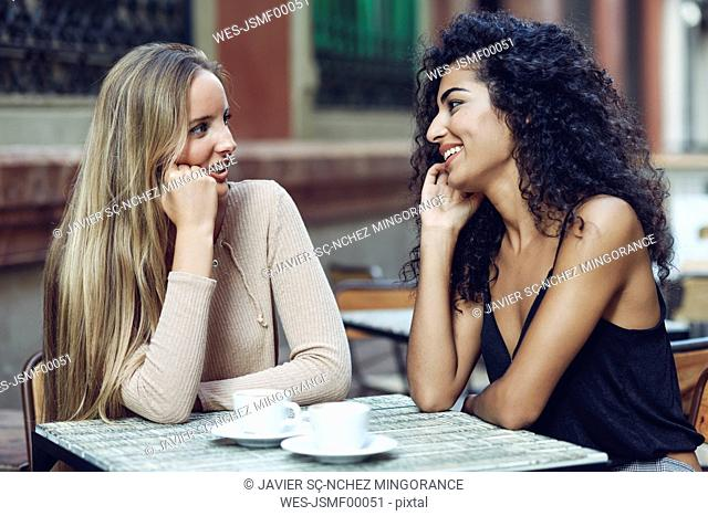 Two friends talking together in sidewalk cafe