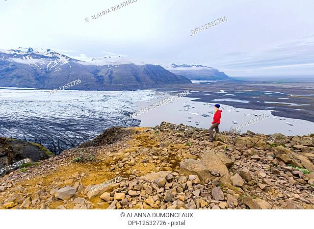 A female hiker in warm clothing for the elements stands on the edge of moutain cliff overlooking the glacier lake and valley views of Vatnajokull National Park;...