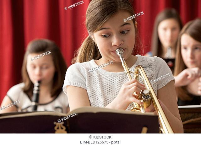 Close up of Caucasian girl playing trumpet on stage