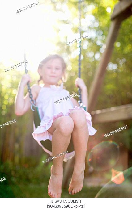 Portrait of girl swinging on garden swing