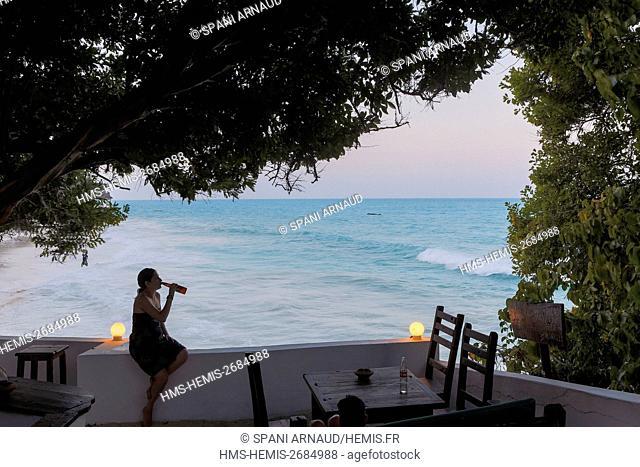 Tanzania, Zanzibar, Jambiani, young woman tourist contemplating the horizon drinking a beer on the terrace of a luxury hotel