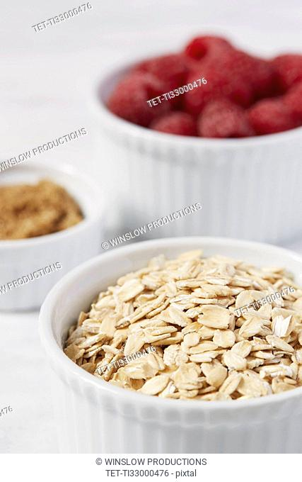 Close up of oats and raspberries in bowls