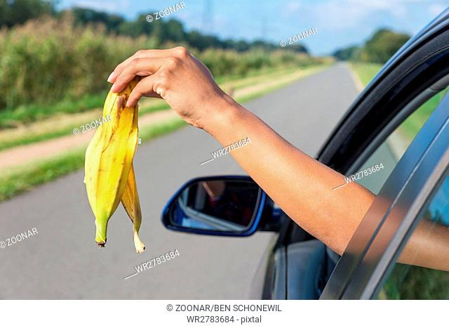 Arm dropping peel of banana out car window
