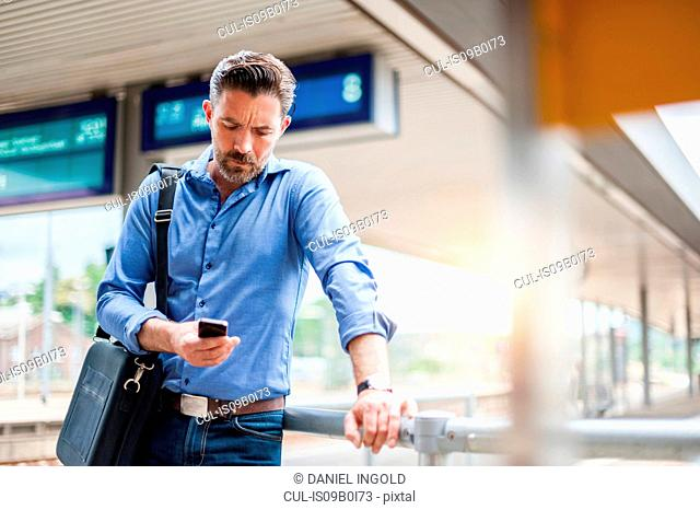 Mature businessman reading smartphone text on railway platform