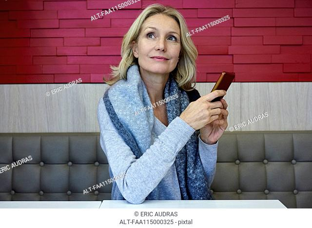 Woman using smart phone in café