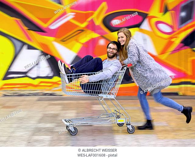 Young woman pushing man in shopping cart, laughing and running