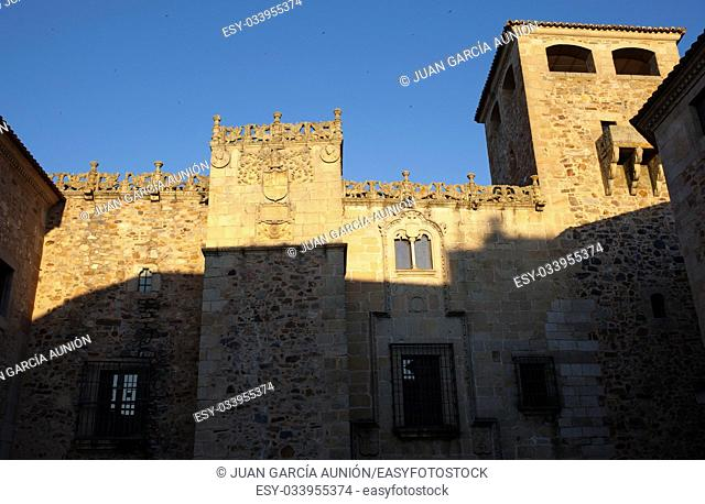 Golfines Palace at sunset. Coat of arms Illuminated by last ray of sun, Caceres, Spain