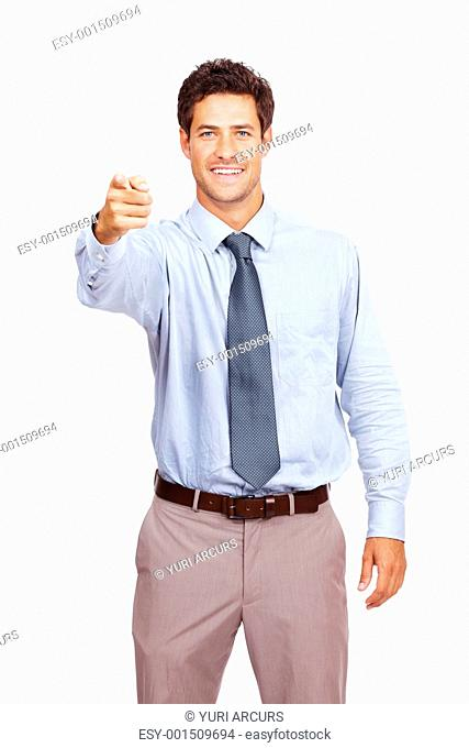 Portrait of a smiling young male business executive pointing at you against white background