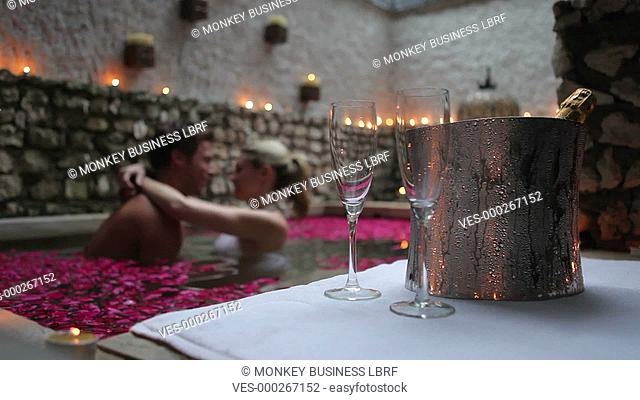 Focus on champagne in ice bucket in foreground as couple embrace in pool.Shot on Canon 5d Mk2 with a frame rate of 30fps