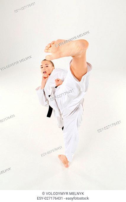 The karate girl in white kimono and black belt training karate over gray background