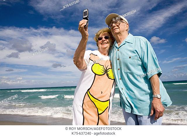 Senior couple taking picture with camera phone