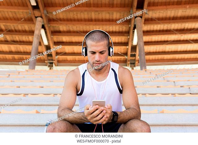 Young sportsman with headphones and smartphone
