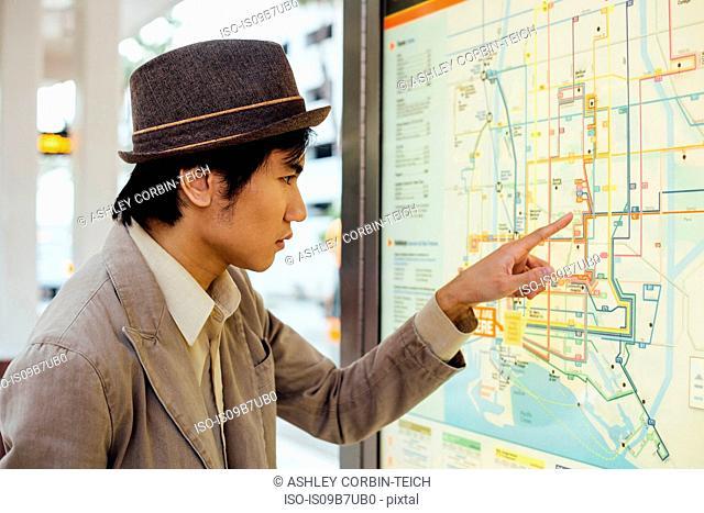 Young man looking at train map at train station