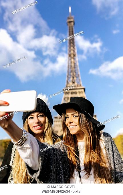 France, Paris, two smiling women taking a selfie with the Eiffel Tower in the background