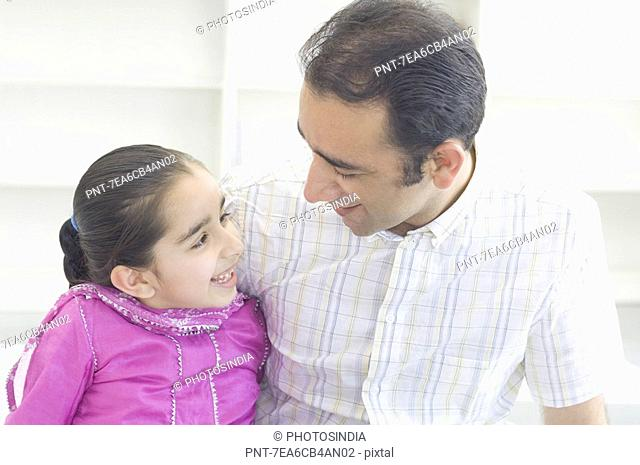Close-up of a mid adult man with his daughter looking at each other and smiling