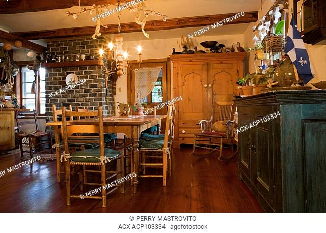 Antique table and chairs in the dining room of an Old Canadiana (circa 1859) cottage style wooden siding Residential home, Quebec, Canada