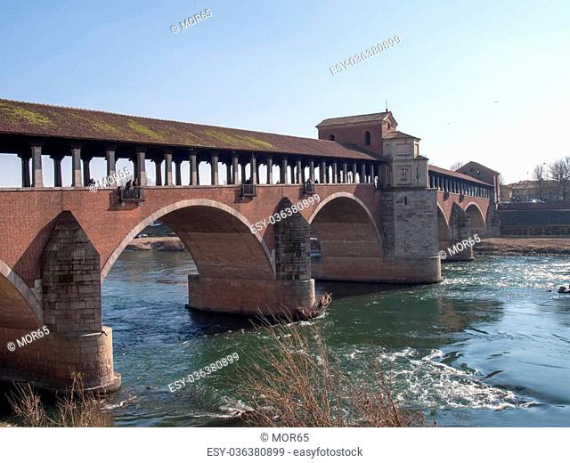 Pavia, Italy - March 8, 2015: Covered bridge over the river Ticino. Very quaint, has five arches and is completely covered with two portals at the ends and a...