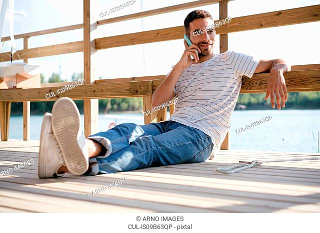 Man relaxing on pier, talking on smartphone
