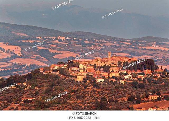 Panoramic view of medieval hilltop town of Monte Castello di Vibio at sunset, with golden light over village and surrounding hills and fields, Umbria, Italy
