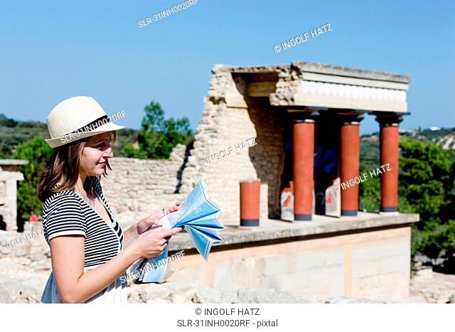 woman looking and holding a map in front of temple
