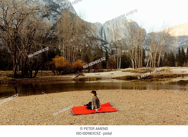 Woman sitting on red blanket looking out at landscape, Yosemite National Park, California, USA