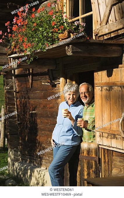 Austria, Karwendel, Senior couple leaning on log cabin, holding mugs