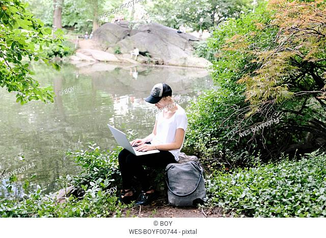 Young woman sitting at lakeside in park using laptop