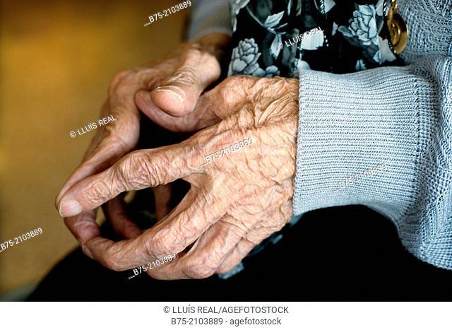 Closeup of a centenarian woman hands in meditation position