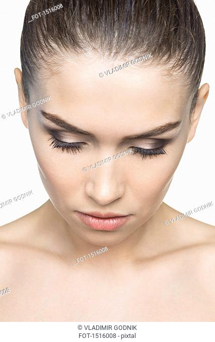 Close-up of beautiful woman looking down against white background