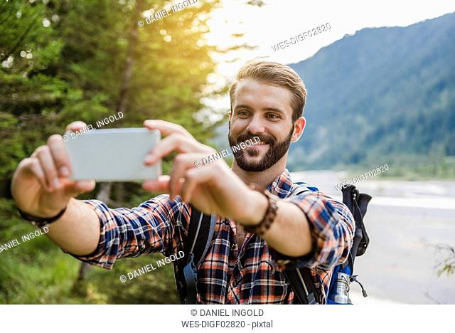 Portrait of smiling young hiker taking selfie with cell phone