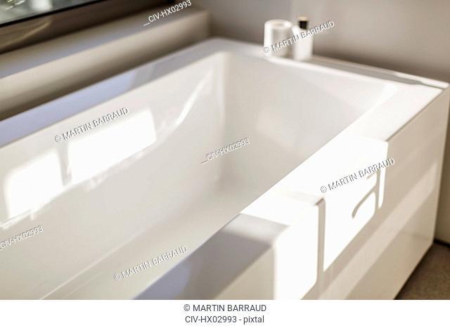 Sunny reflection over modern white bathtub