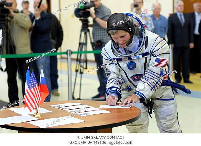 At the Gagarin Cosmonaut Training Center in Star City, Russia, Expedition 48-49 backup crewmember Peggy Whitson of NASA signs in for Soyuz qualification exams...