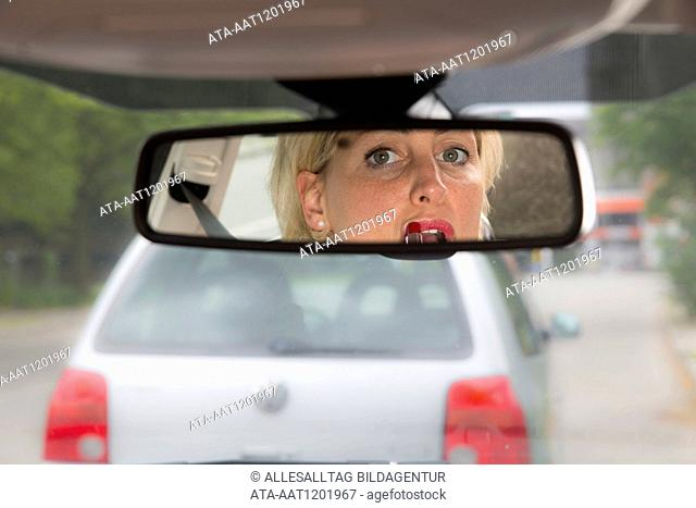 Female car driver puts on lipstick