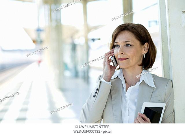Portrait of business woman telephoning on platform
