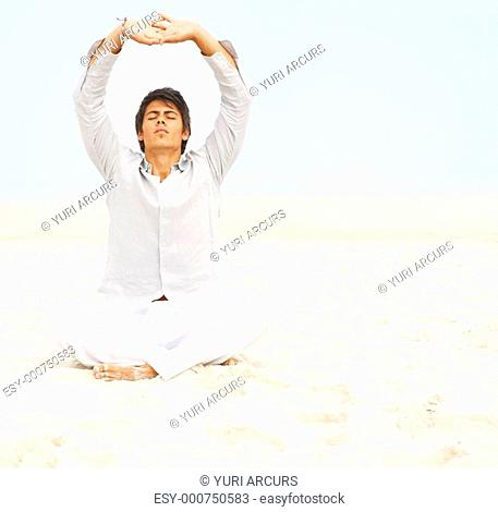 Portrait of a man meditating with his hands together above his head at a beach