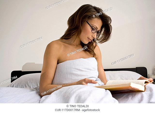 brunette woman in bed reading with glasses.She is sitting up with bed sheet wrapped around her .Daylight lighting, neutral, simple white background