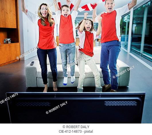 Family cheering in front of television in living room