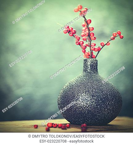 Abstract still life with ceramic vase and red berries