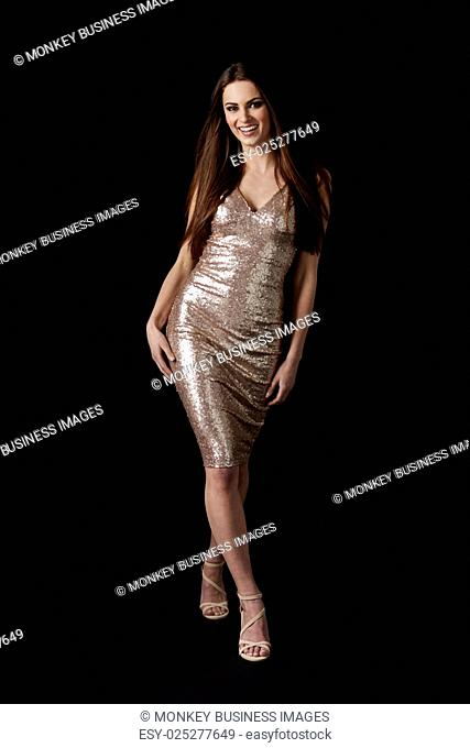 Young dark haired woman in evening dress leaning, vertical