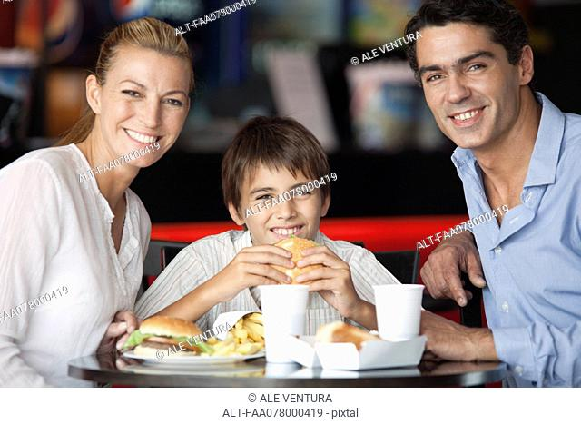 Family eating together in fast food restaurant, portrait