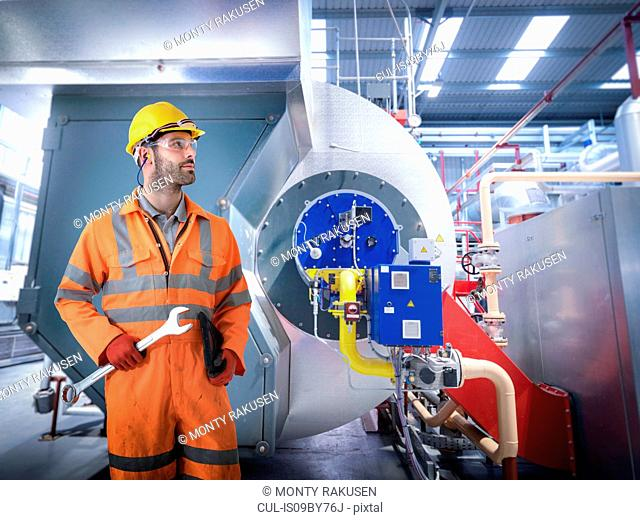 Composite image of engineer with boiler in gas power station