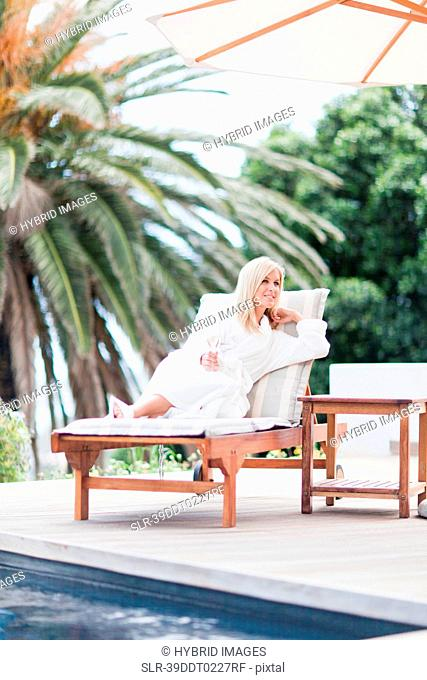 Woman in bathrobe relaxing by pool